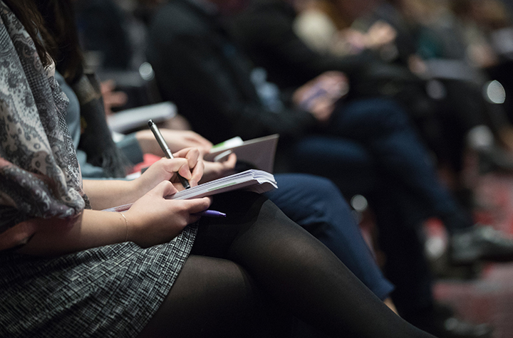 Girl taking notes at an info session